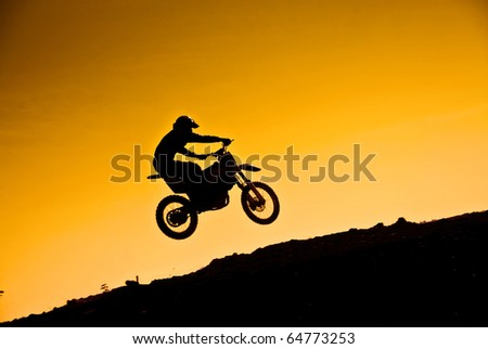 Silhouette of motorcyclist in jump - stock photo
