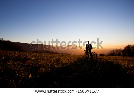 silhouette of mountain biker in sunset  - stock photo