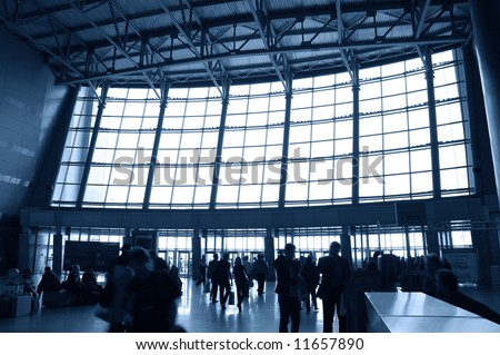 silhouette of moving people in lobby of modern business building - stock photo