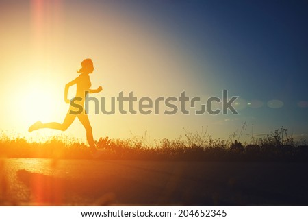 Silhouette of muscular sporty girl running on the beautiful road at amazing bright sunset, female jogger with muscular body at evening run, fitness and healthy lifestyle concept - stock photo