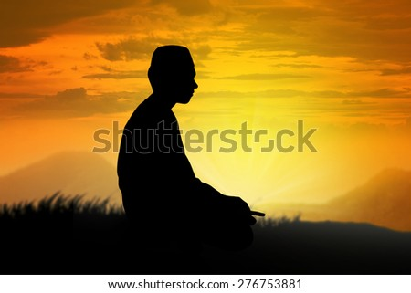 Silhouette of muslim man praying with sunset background - stock photo