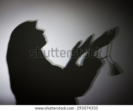 Silhouette of Muslim woman with hijab - stock photo