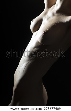 Silhouette of naked body of a young girl on black background, vertical picture - stock photo