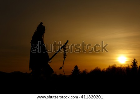 silhouette of native american shaman with pikestaff on background of sunset beautiful in mountains - stock photo