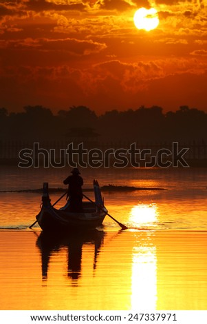 Silhouette of oarsman on boat with broad lake at during sunrise, U-Bein bridge, Mandalay, Myanmar   - stock photo