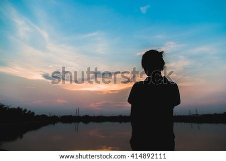 Silhouette of of a little girl on nature background at sunset - stock photo