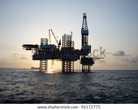 Silhouette of Offshore Jack Up Rig in The Middle of The Sea at Sunset Time - stock photo