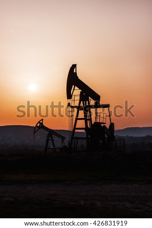 silhouette of oil pump at sunset - stock photo