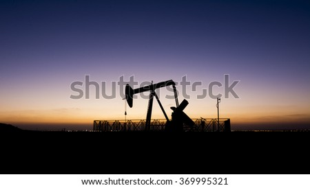 Silhouette of Oil pump at sunset in Bahrain oil field. - stock photo