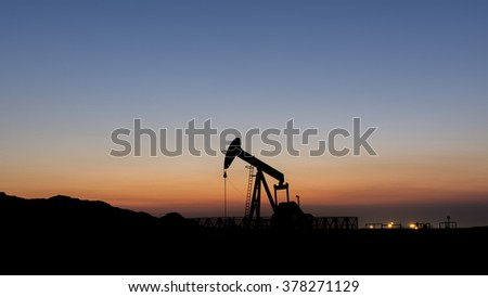 Silhouette of oil pump at sunset in the oil field.