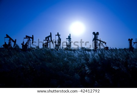 Silhouette of oil pump jacks  with beautiful sunset - stock photo