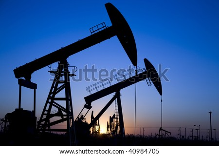 Silhouette of oil pump jacks with sunset - stock photo