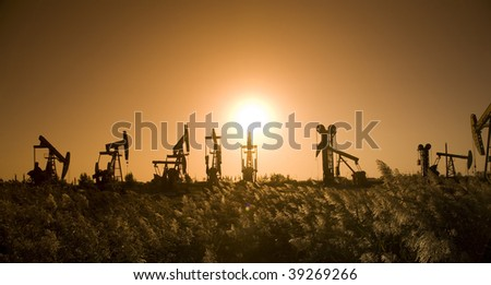Silhouette of oil pump with sunset - stock photo