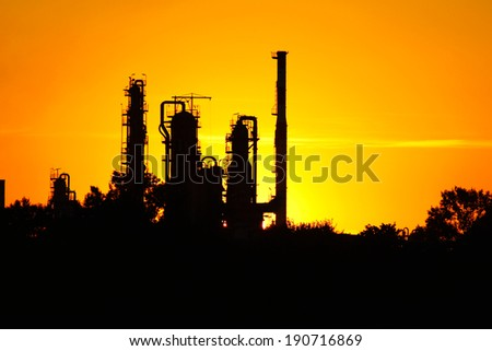 silhouette of  oil refinery factory  against sunset - stock photo