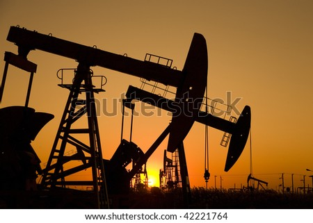 Silhouette of oil well with sunrise - stock photo