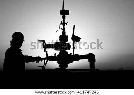 Silhouette of oilfield worker working at wellhead in oilfield - Sunset - Black and white  - stock photo