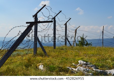 Silhouette of old barb wired borderline high on a mountain height