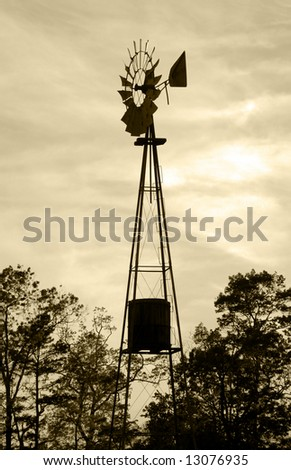 silhouette of old fashioned windmill water tower - stock photo