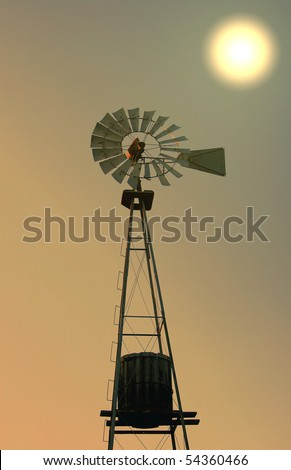 silhouette of old fashioned windmill water tower at sunset - stock photo
