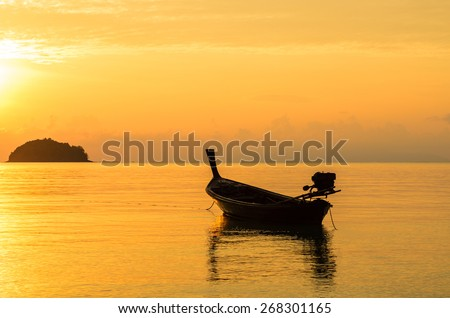 Silhouette of old wooden fishing boat in sunrise, Lipe Island, Thailand.