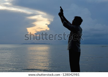 Silhouette of one man shooting short gun with ocean background. - stock photo