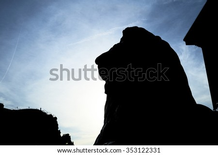 Silhouette of one of the four lions statues that surround Nelson's Column in Trafalgar Square, shot against blue sky. - stock photo