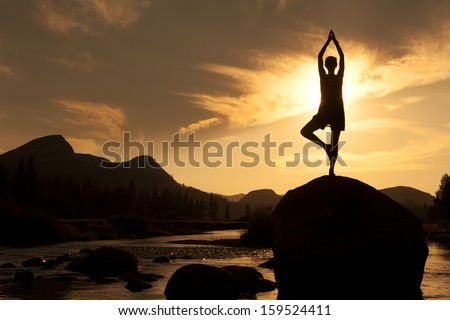 Silhouette of Outdoor Yoga, Young Woman in Tree Pose - stock photo