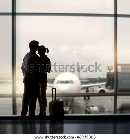 silhouette of pair of lovers near the window in airport - stock photo