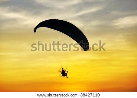 silhouette of para motor glider - stock photo