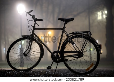 Silhouette of parked bicycle in park at foggy night in autumn