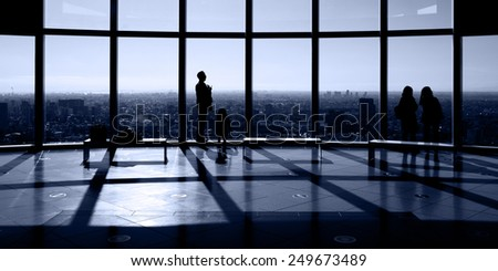 Silhouette of people against a large observation window with view of an urban city skyline.  - stock photo