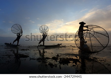 Silhouette of People fishing on Lake Inle in sunrise with fog at Burma, Myanmar  - stock photo
