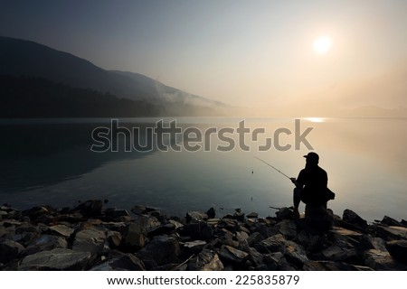 Silhouette of people fishing on the lake with mist at sunrise - stock photo