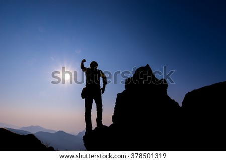 Silhouette of people Hike on the peak of rocks mountain at sunset with arms raised up above head in celebration