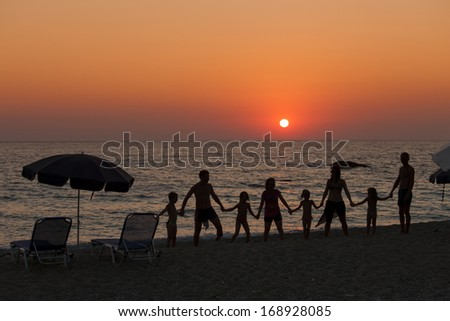 Silhouette of people holding hands on beach on sunset