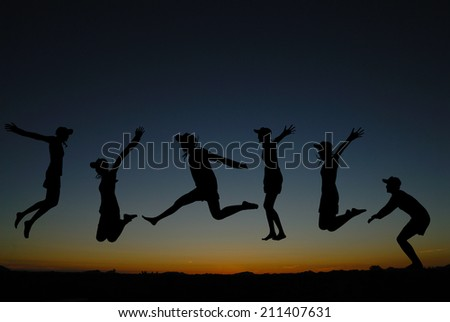 silhouette of  people jumping at sunrise  - stock photo