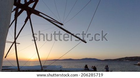 silhouette of people looking at the sunset from the windmills of mykonos island,Greece