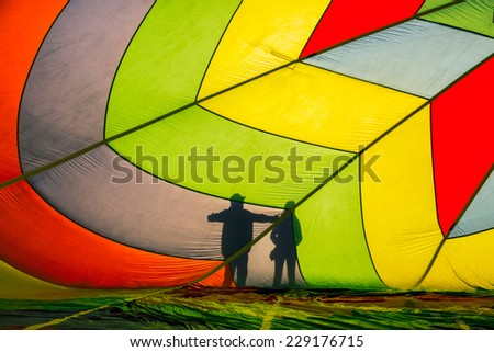 Silhouette of people outside hot air balloon - stock photo