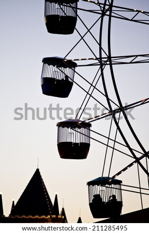 Silhouette of people riding on a ferris wheel - stock photo