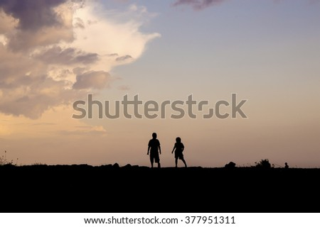 Silhouette of people standing on the hill at sunset