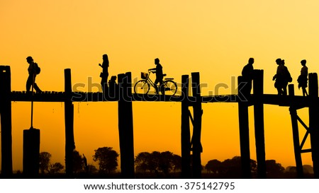 silhouette of people traveling across the U Bein Bridge in the evening. U bein bridge, Taungthaman lake, Amarapura, Burma. It is the oldest and longest teak wooden bridge in the world