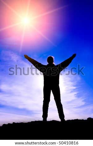Silhouette of people with arms outstretched to the sky - stock photo