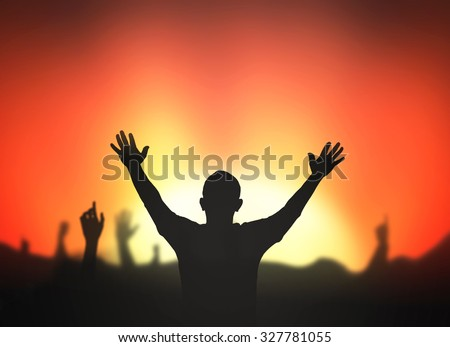 Silhouette of people with hands raised to beautiful red sunset background. - stock photo