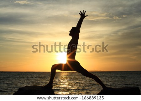 Silhouette of perfect body man acts yoga on the rock with sea sunset background - stock photo