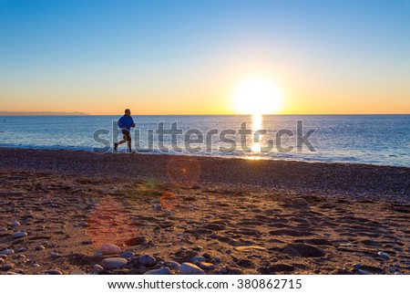 Silhouette of Person Jogging along Ocean Beach at Sunrise orange and blue tones