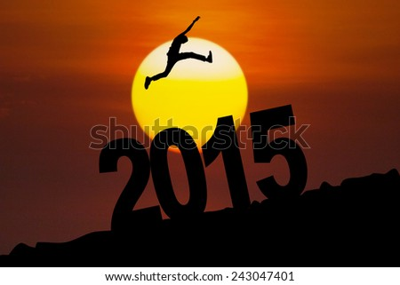 Silhouette of person jumping above number 2015 at sunset time - stock photo