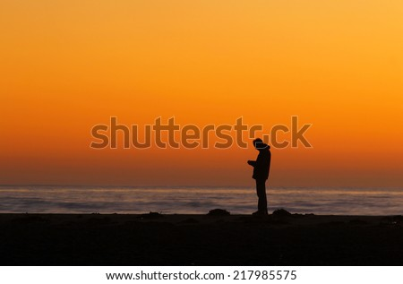Silhouette of person looking at phone at sunset - stock photo