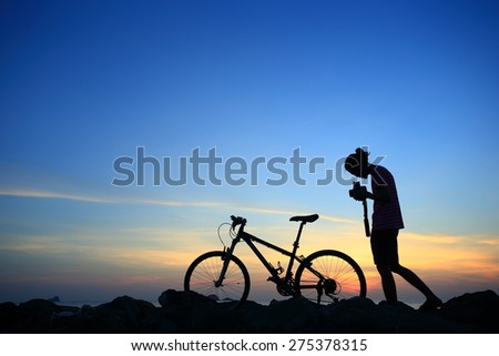 Silhouette of photographer in action take photo with his bike on rock mountain with sunrise twilight background. Symbol of relax, success and touring. - stock photo