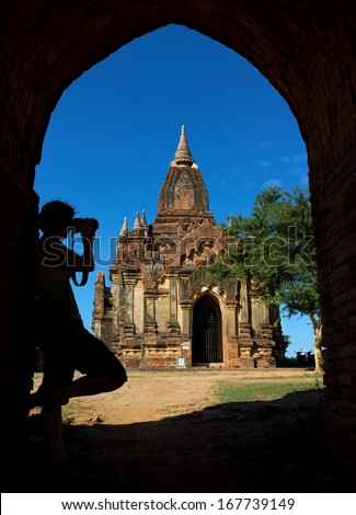 silhouette of photographer in arch at the entrance to pagoda, Bagan, Myanmar(Burma), november 2014 - stock photo