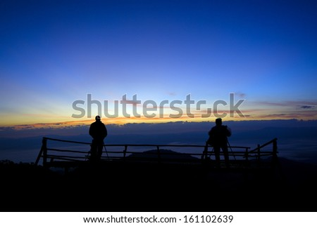 Silhouette of photographer on the top of mountain.